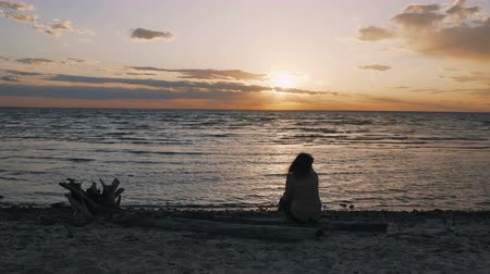хот дог : A sad girl sits on the sea shore on a log and looks at the sunset. 4к
