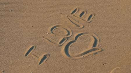 hashtag : Inscription love on sanThe inscription on the sand I love, the symbol of love.d. Stock Footage