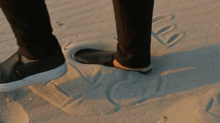 hashtag : The inscription on the sand I love, on which the foot steps. close - up, slow motion.