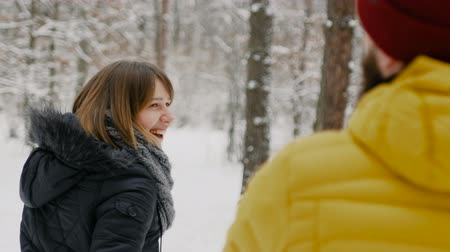 Love and happy young couple holding hands on a walk in a winter park Stok Video