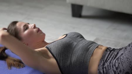 A young girl engaged in fitness at home. The girl does sports exercises on the mat. A young girl shakes her abdominal muscles on the mat. Slow motion.