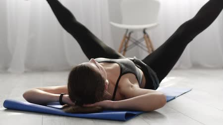 A young girl engaged in fitness at home. Girl doing sport exercises lying on the mat. Slow motion.