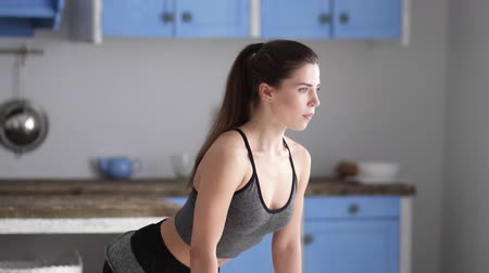 squat : A young girl engaged in fitness on the background of the kitchen. Girl does fitness exercises at home. The girl crouches. Slow motion Stock Footage