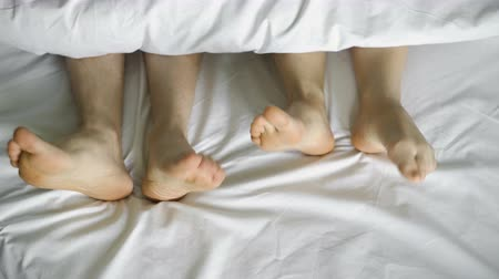матрац : Feet dancing under a white blanket, on a white bed, top view.4k Стоковые видеозаписи