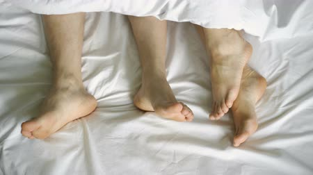 couple in bed making love. male and female legs top view, white linens. sex, 4k