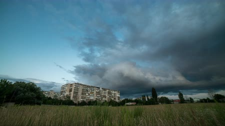 Time lapse storm clouds pass over residential buildings, the outskirts of the city from right to left. ProRes 4K.