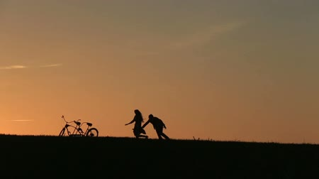carinho : Silhouette of  Beautiful Couple With Tandem Bicycles Playing Catch  Against  Sunset On The Background Close Up Vídeos
