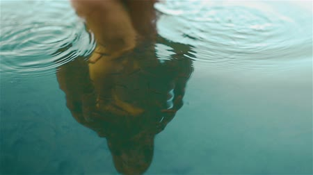 smyslnost : Young naked carpathian nymph plays with little fishes in the beautiful clean blue water of Synevir mountain lake. Reflection of naked woman body in the calm blue water close up. Slow motion shot Dostupné videozáznamy