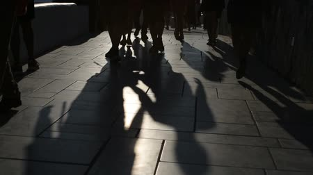 одиноко : Shadows of people walking in city. Street procession.