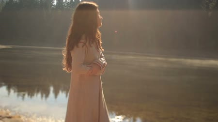девственница : Mystic young girl with long dark hair at the mysterious mountain lake Synevir in Carpathians. Beautiful nimph enjoys the mountain landscape and basks on the sun