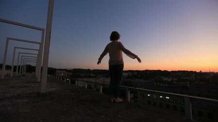 an : Silhouette of young woman raising hands to sun at sunset. Moment of freedom and happines. Young woman meditates on the bridge with city landscape background