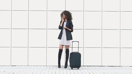 teljes hosszúságú : Portrait of beautiful african american businesswoman talking by phone on white textured wall background. Black woman with luggage in airport