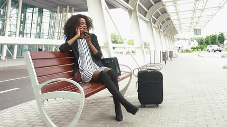 podróżnik : Portrait of attractive young smiling african american business woman sitting on the bench at the airport and talking on cellphone