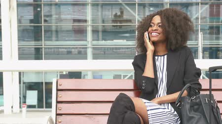 tek başına : Fabulous smiling african american business woman sitting on the bench at the airport and talking on cellphone while waiting for a flight. Urban glass wall background Stok Video
