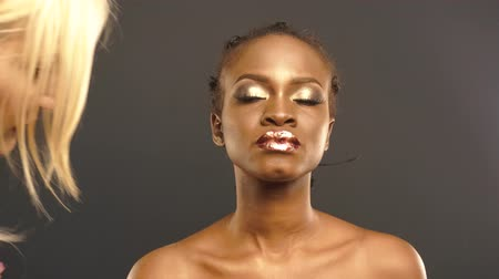 brazen : Glint. Coloring. Mysterious African American Woman with Golden Faceart Preapring For Shooting With Stylist. Creative Surreal Concept Stock Footage