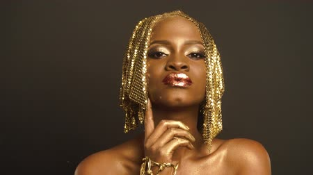 brazen : Studio Portrait of Surreal African American Woman with Golden Faceart Preapring For Shooting With Stylist. Creative Vogue Concept Stock Footage