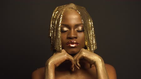 gerçeküstü : Big close-up portrait of surreal mysterious black african american female model with golden faceart and big glossy lips. Creative surreal concept