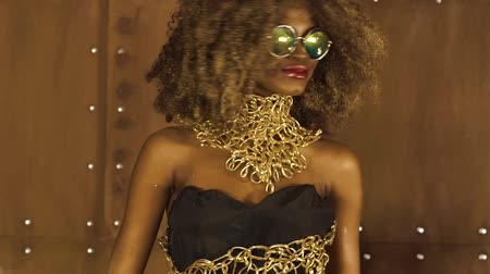 coroa : Magic surreal golden african american female model in massive sunglasses with bright glitter makeup, glossy golden hairstyle and big red lips posing on the studio background Vídeos
