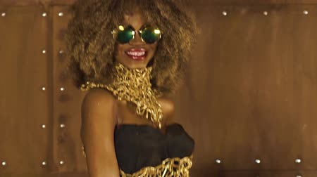 черные волосы : Magic surreal golden african american female model in massive sunglasses with bright glitter makeup, glossy golden hairstyle and big red lips posing and laughing on the studio background Стоковые видеозаписи