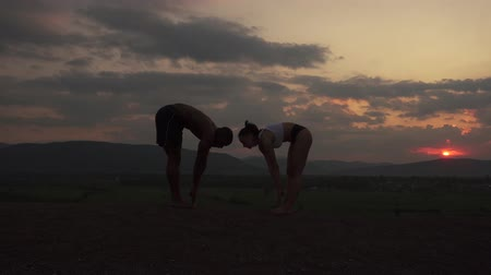 trabalhar fora : Silhouettes of fit mixed race couple stretching together on the rocky mountains background. Sport fitness concept