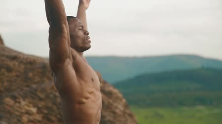 nipple : Side view of handsome african american bodybuilder stretching outdoor. Mountain landscape background