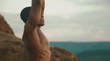 nipple : Side view of strong african american bodybuilder stretching outdoor. Mountain landscape background Stock Footage