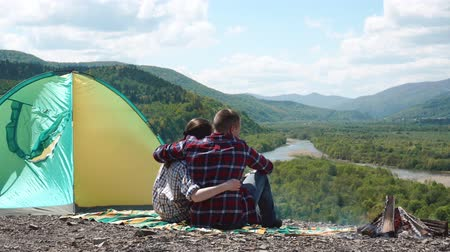 sátor : Young tourist couple hugging at camp site with bonfire on rocky top of hill in green mountains