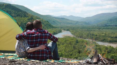 sátor : Romantic tourist couple hugging at camp site with bonfire on rocky top of hill in green mountains