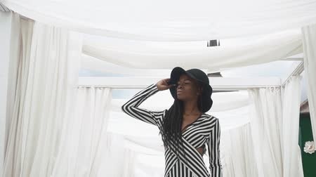 африканского происхождения : Afro-American young woman in fashionable striped cocktail dress posing on the background of her luxury apartments Стоковые видеозаписи