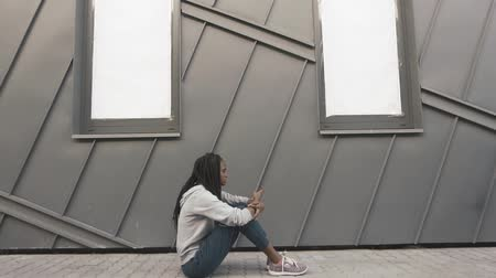 беспокоюсь : Young african american woman looking sad and choose music to listen on her phone. Grey wall background Стоковые видеозаписи
