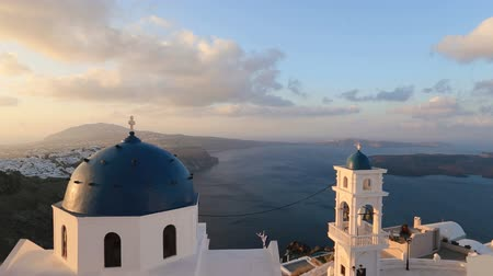 aegean sea : Santorini Church with blue dome by Aegean Sea. Church bells on Santorini island which is one of the famous tourist attraction. Time lapse