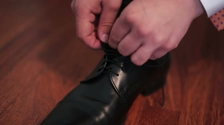 couro : Mans hands tiyng black leather shoe