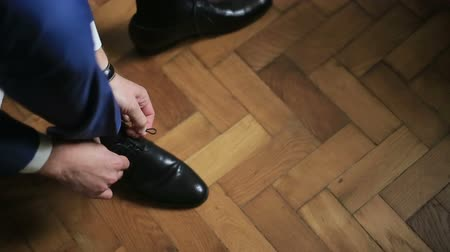 cipőfűző : Man in blue suit tying black leather shoes preparing for formal event