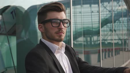 беспокоюсь : Side view of an attractive businessman takes off glasses and being worried and thoughtful while standing next to office buildings in a classic city square. Стоковые видеозаписи