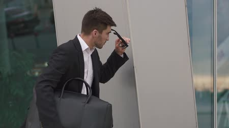 neurotic : Anxious young businessman in glasses hiding from someone at the wall. Urban city background