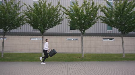 çabaları : Young handsome businessman with beard running with big suitcase in slowmotion. Urban city background