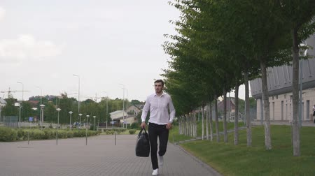 efforts : Front view of handsome businessman with beard running with big suitcase in slowmotion. Urban city background Stock Footage