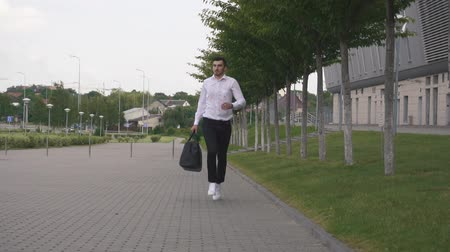 çabaları : Front view of handsome elegant businessman in white shirt running with big suitcase in slowmotion. Urban city background Stok Video