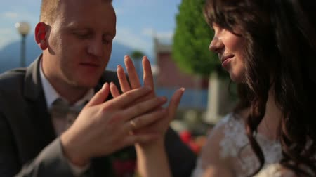 halkalar : Groom softly touches brides hand close up. Lake Como, Italy on background