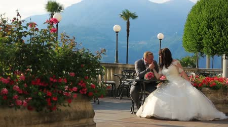 nevěsta : Groom kisses brides hand in the summer cafe. Honeymoon in the Como, Italy