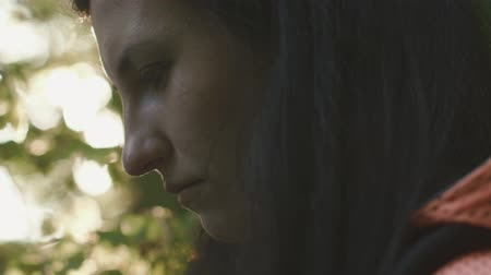 haughty : Big close-up of serious sad brunette woman lit by sun looking ahead on a sunny summer day in the forest Stock Footage