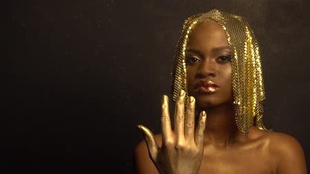 yansıma : Fashion Portrait of Glossy African American Woman with Bright Golden Makeup Surrounded by Golden Dust. Bronze Bodypaint, Black Studio Background