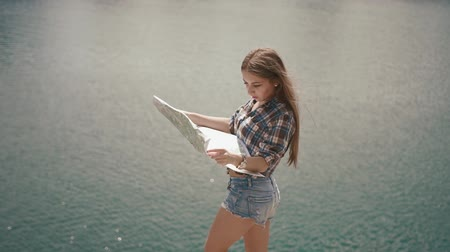 шорты : Young active backpacker girl checking with map near water surface of mountain lake at sunny day