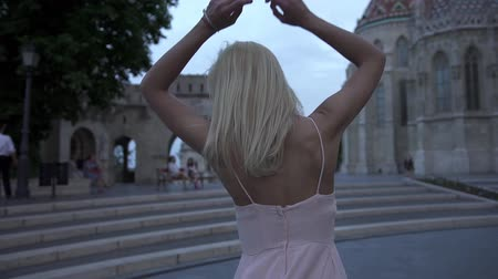 pięta : Charming sexy blonde wearing a sexy pink dress walking in Budapest and enjoying the cityscape panorama at twilight