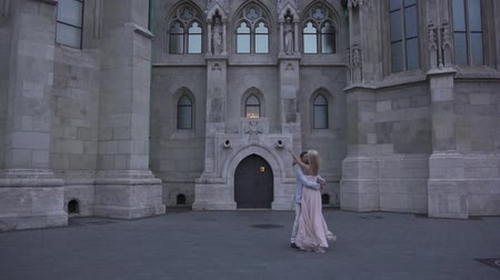 fantasia : Handsome man spinning his beautiful girlfriend in long elegant pink dress near the magnificent castle in Budapest, Hungary