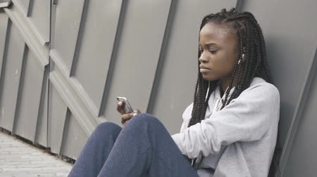 kulaklar : Young adult woman listening music on smartphone through earphones after training