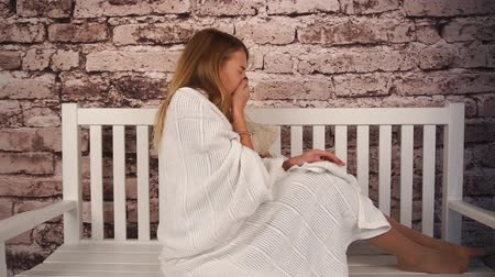 menstruáció : young teenage girl feeling sick. She sitting on the bench, hugging a teddy bear and sneezing. Covered her body with white coverlid Stock mozgókép