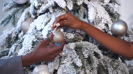 Рождественский бал : Black msn give decorative ball to black woman. Couple decorated Christmas tree