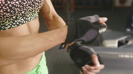 sztuki walki : Beautiful fit woman is putting on gloves for training Wideo