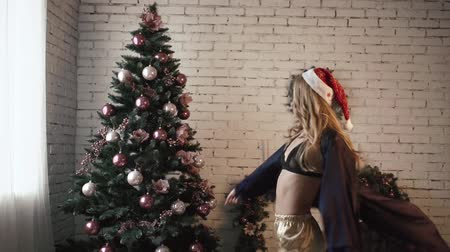good new year spirit : Young beautiful girl in sexy lingerie is whirling near the Christmas Tree